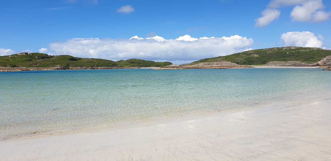 White sand beach at Knockvologan with gentle waves, turquoise sea, distant hills and blue skies