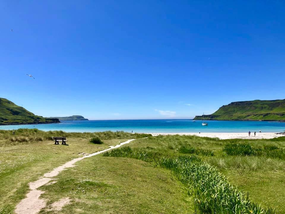 Sandy path leads through the sand dunes and grassland to Calgary Bay, with turquoise sea and blue skies.