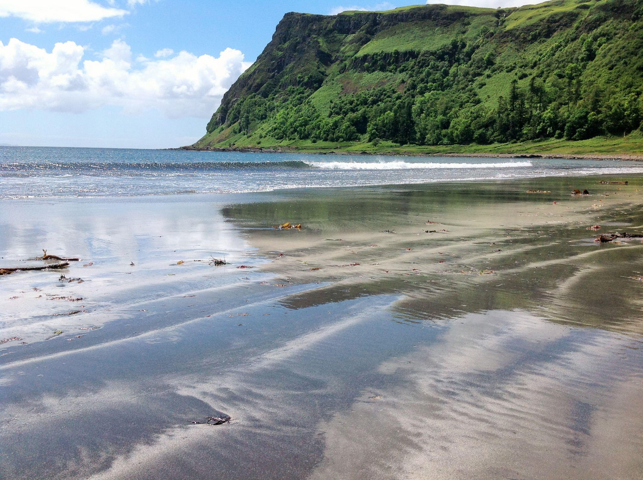 The grey sand beach at Carsaig, surrounded by a lush green headland and blue clouded skies as the waves lap on shore