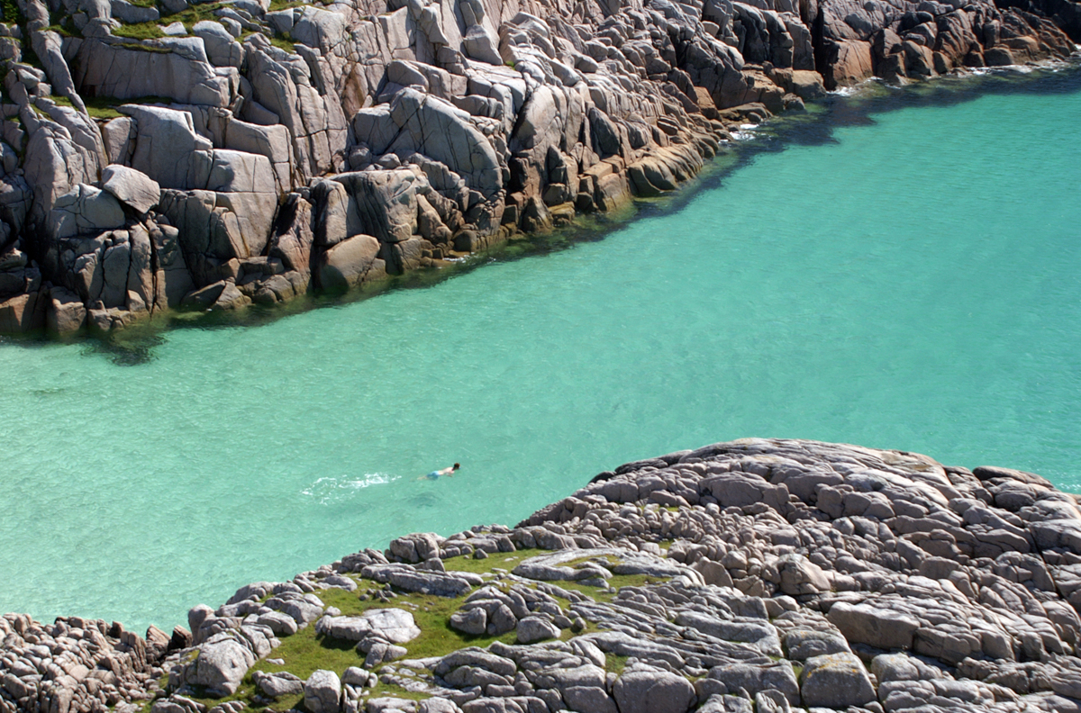 Swimmer exploring the bay between two rocky headlands in turquoise clear seas