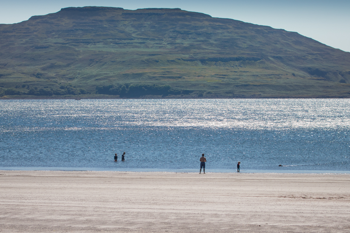 Wild swimmers enter the sea at Traigh na Cille, the black beach on the Isle of Mull