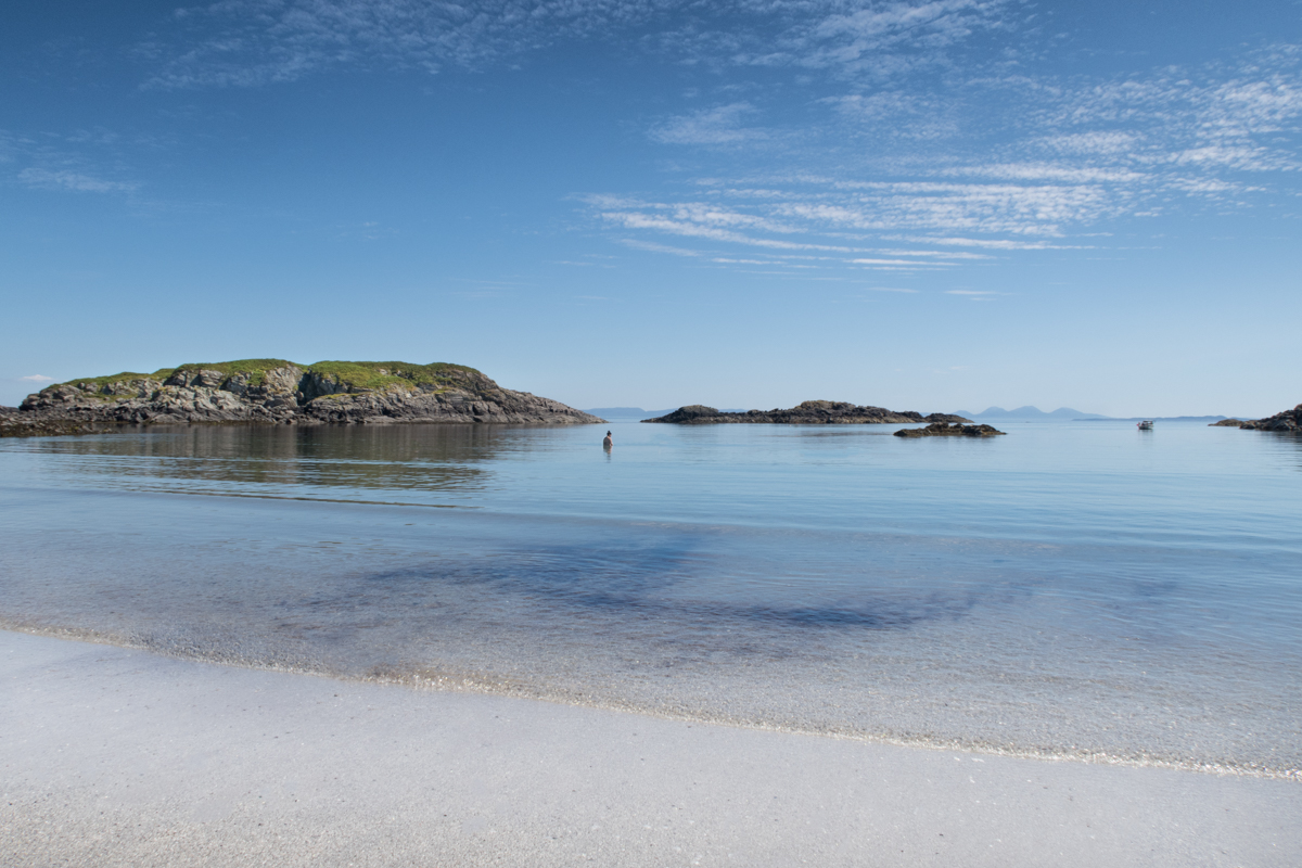 Wild swimmers enjoying the calm sea and turquoise blue skies on Uisken beach in Mull