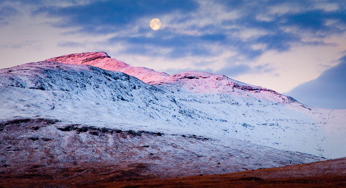 Winter on the Isle of Mull with snow-covered mountains, blue skies and the moon above