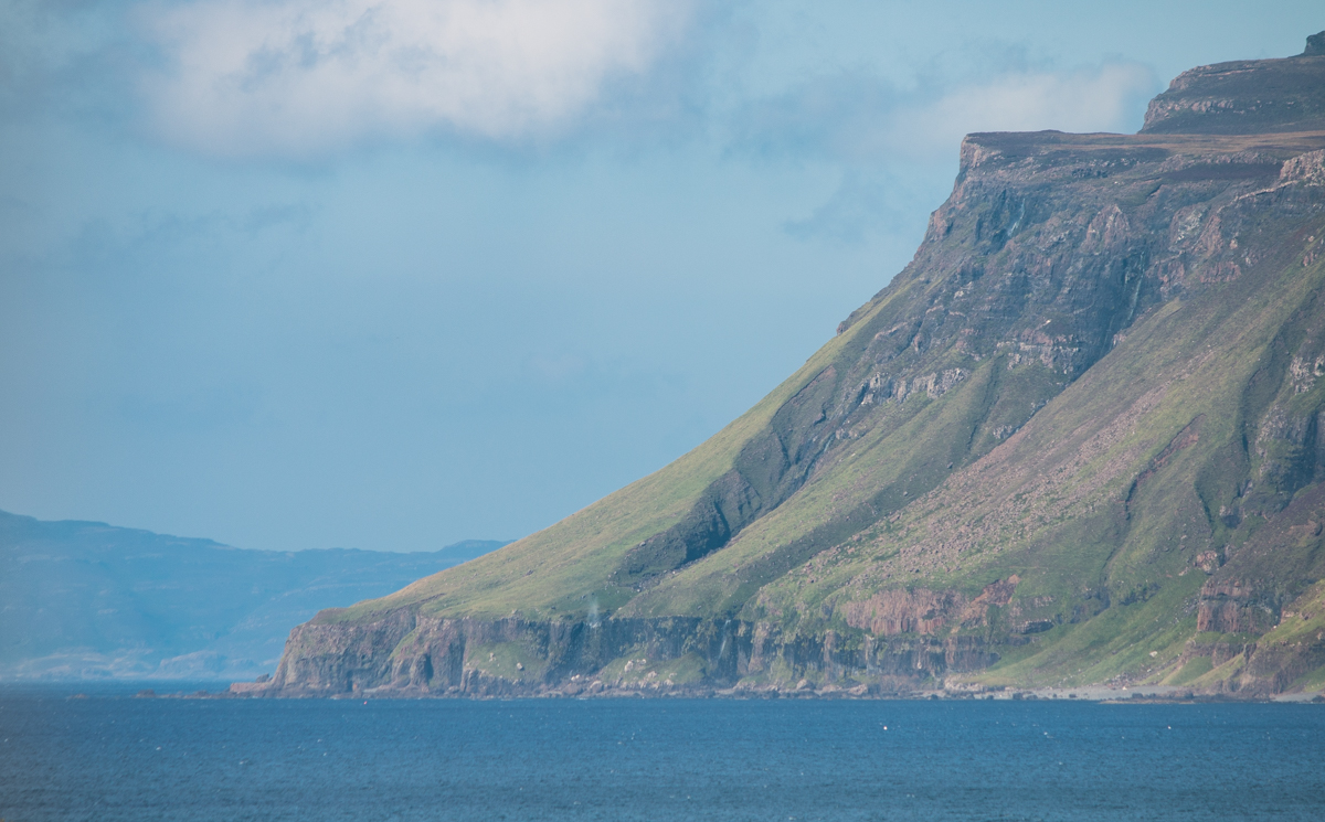 Ardmeaneach peninsula wilderness headland meeting the sea at Loch Scridain with steep cliffs and blue skies above
