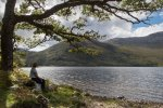 A walker enjoying the peace and quiet at one of the pebble bays on Loch Ba