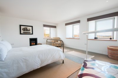 Double bedroom on ground floor with wood stove and seating