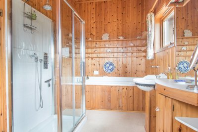 En-suite bathroom with large shower unit and separate bath
