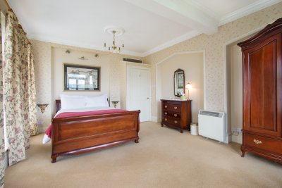 Large double bedroom with king sized bed and luxurious bed linen, towels and robes