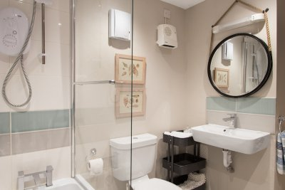 Contemporary bathroom with bath, electric shower, basin and w.c.