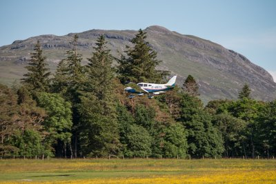 Light aircraft landing on the airfield in front of the house