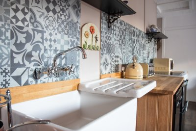 The compact kitchen area has a quirky cottage style