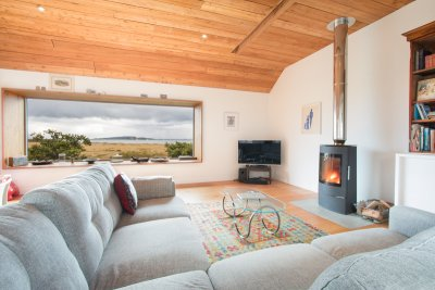 Wood burning stove and window framing the fantastic view from the living area