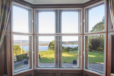 Large windows overlooking the front lawn with sea beyond