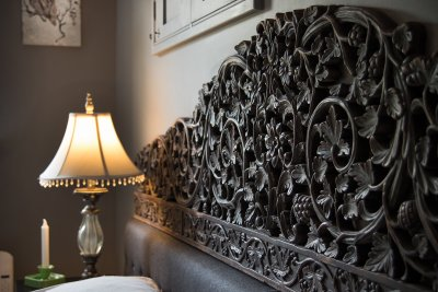 Carved headboard and beautiful vintage pieces add to the ambience