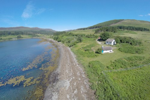 The Bothy and Dorran positioned by the coastline
