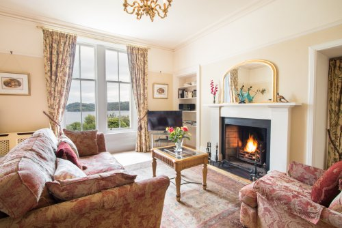 Columba Apartment living room with open fire and opulent furnishings and antiques