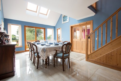 Dining table in the main hall space with doors leading to the garden