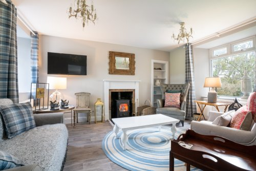 Sunshine or showers, the cosy living room promises the perfect spot to curl up beside the wood burning stove