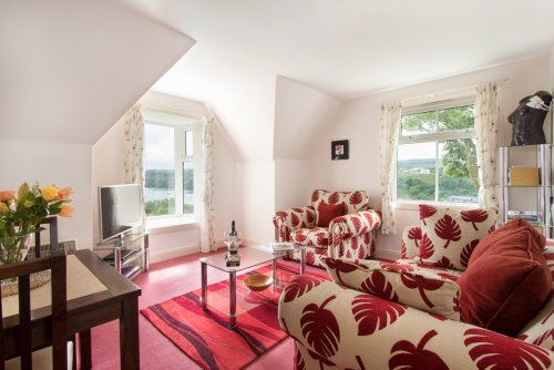 Living room with dual aspect windows, letting in lots of natural light, with excellent views of Tobermory harbour