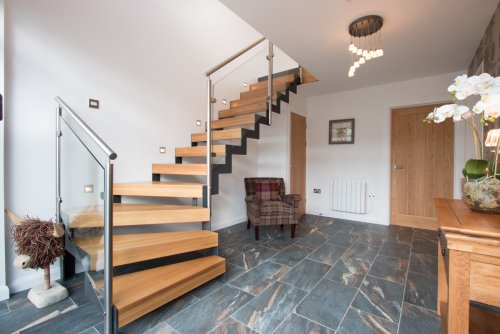 Entrance hallway with stairs, leading to bedroom, bathrooms and large utility room