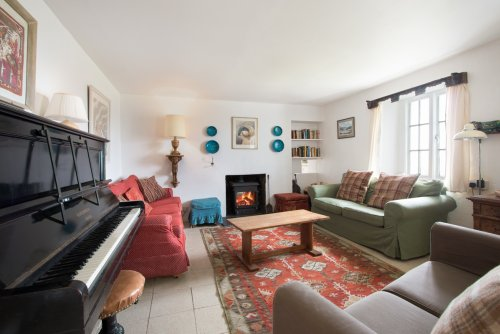 Living room at Tigh na Caora with wood stove, piano, books and games